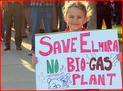 Girl holding sign: Save Elmira, No Bio-Gas Plant